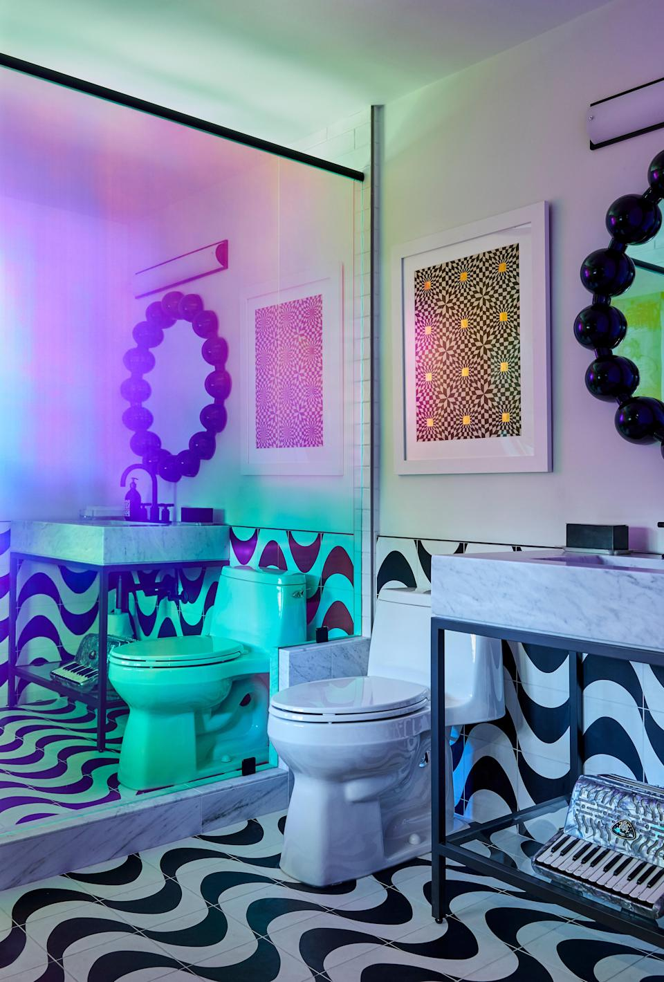 "The bathroom right off Miley's music studio doubles as a storage unit. Explains Tish: ""People are always bringing guitars and their cases, and Miley is very much like me—she wants everything put away. Since some people come and work there for days, we decided to put this opaque film [3M's Dusted Crystal and Dichroic Chili] on the shower glass in order to conceal all the guitar cases and things that might need extra space."" A mirror from Tish's own home hangs in plain view. ""That mirror was actually mine for the last 15 years. Miley always loved it,"" says Tish. ""So when we finished the room, I just took it out of my house and put it there."" Cement black-and-white Rio tiles are by Clé."