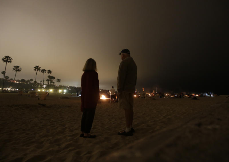 Barbara Peters, left,and her husband Frank pose for a picture near the fire pits on, Sunday, April 28, in Newport Beach, Calif. Air quality regulators are considering a proposal to ban beach bonfires in Southern California due to health concerns. (AP Photo/Chris Carlson)