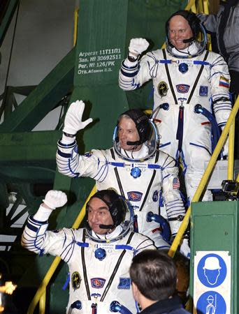 Members of the International Space Station (ISS) crew, Russian cosmonauts Alexander Skvortsov (L) and Oleg Artemyev (R) and U.S. astronaut Steven Swanson (C) wave as they board the Soyuz spacecraft before their launch at the Baikonur cosmodrome March 26, 2014. REUTERS/Vasily Maximov