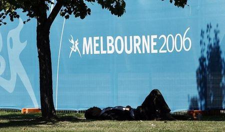 Local resident sleeps in afternoon shade outside venue for Commonwealth Games in Melbourne