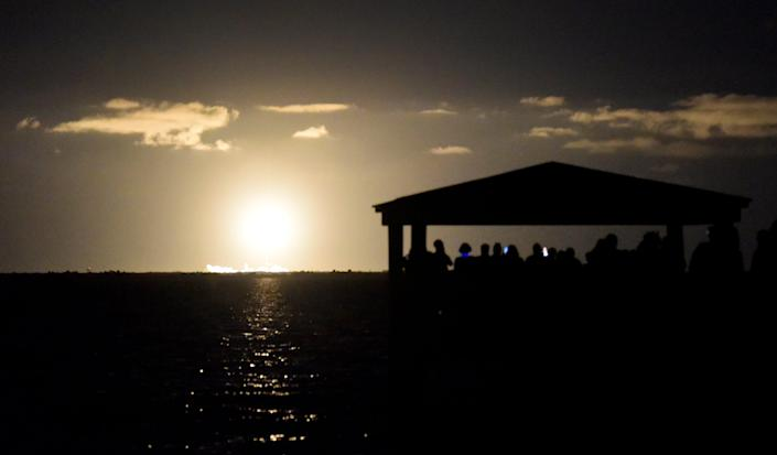 Spectators at Space View Park along the Indian River Lagoon in Titusville, Florida watch the SpaceX Falcon 9 rocket launch.
