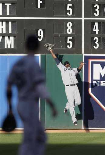 Seattle Mariners left fielder Carlos Peguero, rear, catches a fly ball hit by Oakland Athletics' Coco Crisp during the first inning of a baseball game in Oakland, Calif., Friday, July 6, 2012. (AP Photo/Jeff Chiu)