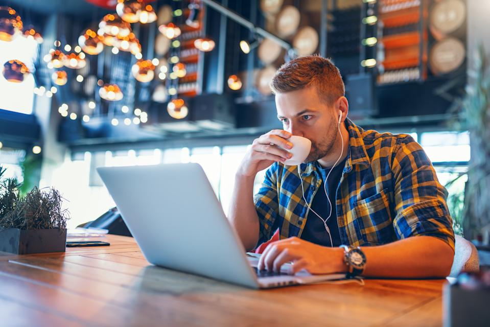 Young Caucasian blogger with earphones in ears and in plaid shirt drinking coffee and using laptop while sitting in coffee shop.