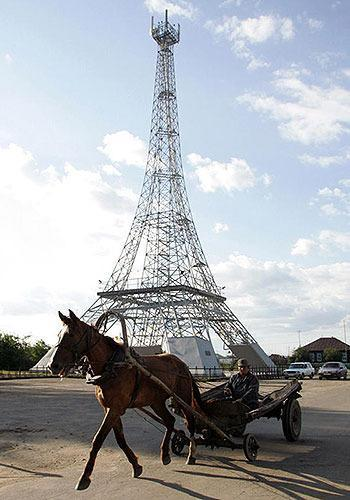 RUSSIA: A horse and cart passes by a 50-meter copy of the Eiffel tower in the village Parizh (Paris) 59 miles southeast of Russia's Siberian city of Magnitogorsk, July 15, 2005. The village bears the name of the French capital since its foundation in the 19th century by Russian Cossaks who had returned from Paris after defeating Napoleon army. The tower was built by the local communication company as a tower for their equipment and a possible tourist attraction.