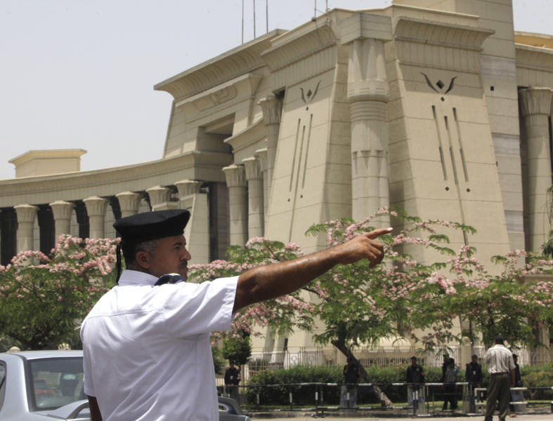 An Egyptian traffic policeman manages the traffic in front of the Supreme Constitutional Court in Cairo, Egypt, Sunday, June 2, 2013. An Egyptian court ruled on Sunday that the nation's Islamist-dominated legislature and constitutional panel were illegally elected and that the legislature's upper house, the only one currently sitting, must be dissolved when parliament's lower chamber is elected later this year or early in 2014.(AP Photo/Amr Nabil)