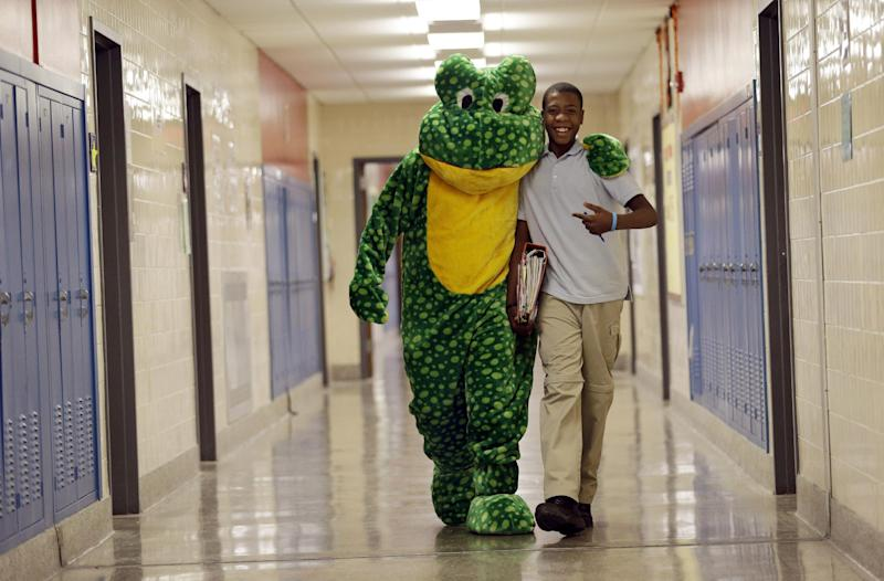 In this Friday, March 1, 2013 photo, Bill Fulton, dressed as Ready Freddy, hugs student Twandrell Dean on his way to visit a prekindergarten class at a public school in Buffalo, N.Y. President Barack Obama's proposal to expand access to preschool is seen as a way to close the achievement gap for poor and minority students, improve high school graduation rates and ultimately strengthen the workforce. (AP Photo/David Duprey)