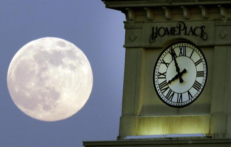 """A """"supermoon"""" rises behind the Home Place clock tower in Prattville, Ala., Saturday, June 22, 2013. The biggest and brightest full moon of the year graces the sky early Sunday as our celestial neighbor swings closer to Earth than usual. While the moon will appear 14 percent larger than normal, sky watchers won't be able to notice the difference with the naked eye. Still, astronomers say it's worth looking up and appreciating the cosmos. (AP Photo/Dave Martin)"""
