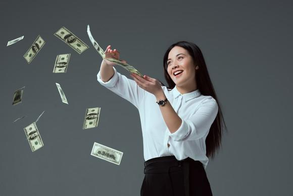 Well-dressed young woman flipping $100 bills off a stack.