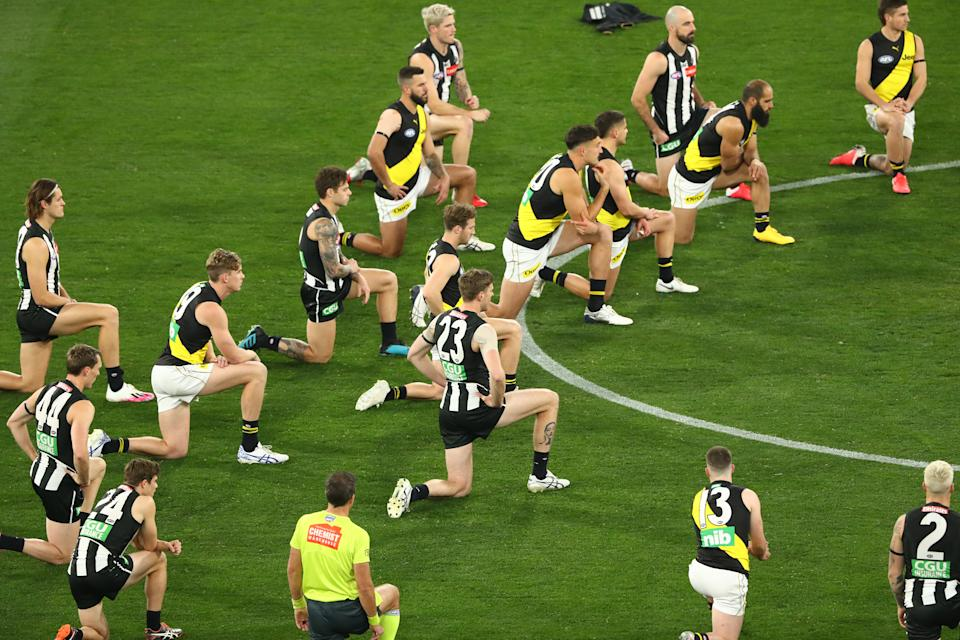 AFL players and umpires are seen kneeling on the pitch before a match