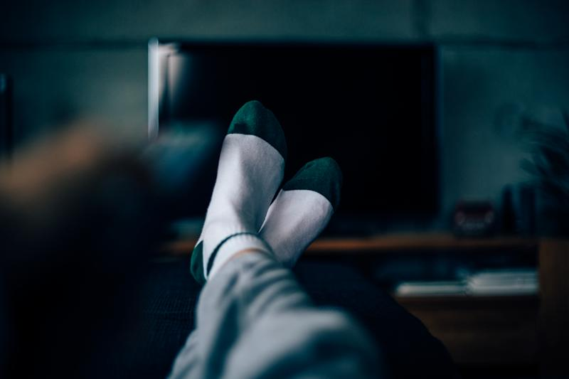 Personal perspective of a woman, feet with socks on and legs extended. Watching TV late at night. Insomnia.