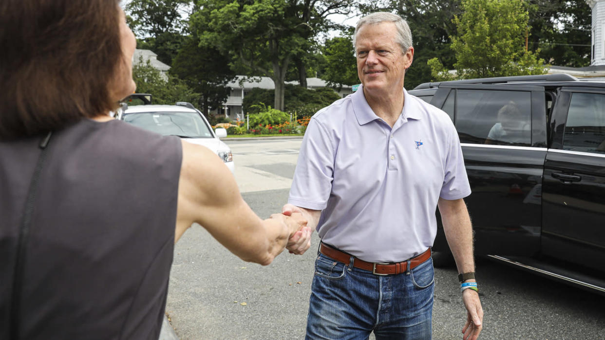 Gov. Charlie Baker shakes the hand of Holly Grant, CEO at American Red Cross of Massachusetts, while arriving with his wife, Lauren, to donate at a Red Cross blood drive at the Magnolia Library and Community Center in Gloucester on July 1, 2021. (Erin Clark/The Boston Globe via Getty Images)