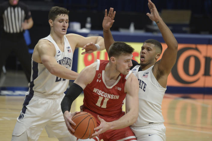 Penn State's John Harrar, left, and Myles Dread, right, pressure Wisconsin's Micah Potter, center, in the second half of an NCAA college basketball game, Saturday, Jan. 30, 2021, in State College, Pa. (AP Photo/Gary M. Baranec)