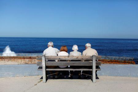 Elderly couples view the ocean and waves along the beach in La Jolla