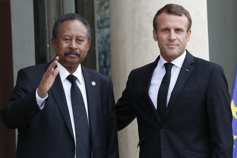 FILE - In this Sept. 30, 2019 file photo, French President Emmanuel Macron, right, welcomes Sudanese Prime Minister Abdalla Hamdok prior to a meeting at the Elysee palace in Paris. Sudan's new, transitional authorities have six months to make peace with the country's rebels under a power-sharing deal reached this summer between the military and the pro-democracy movement following the ouster of longtime autocrat Omar al-Bashir in April. Ahead of talks with rebels to officially start Monday, Oct. 14, 2019, in Juba, the capital of South Sudan, Khartoum has been in a flurry of diplomacy, with Sudanese leaders visiting France, Saudi Arabia and the United Arab Emirates this week to enlist their support. (AP Photo/Thibault Camus, File)