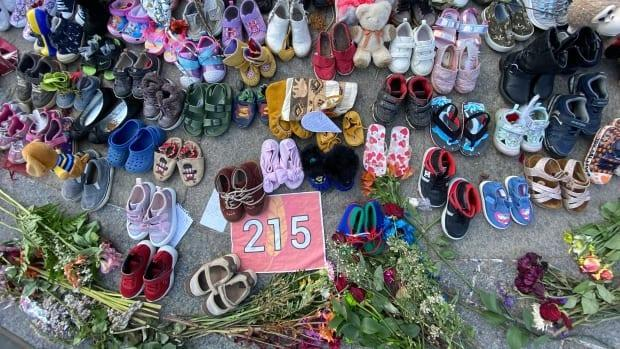 Shoes and flowers laid at a memorial on Parliament Hill to honour the estimated 215 children found buried on the grounds of the former Kamloops Indian Residential School. (Andrew Lee/CBC - image credit)
