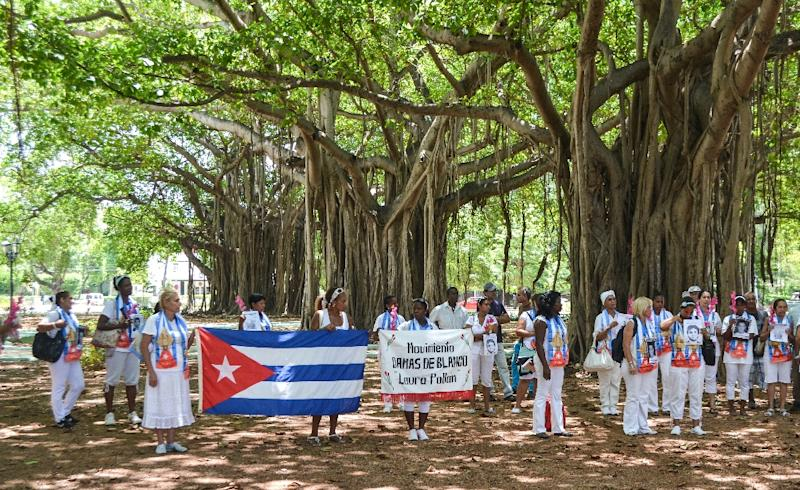 Cuban dissidents and members of the Ladies in White human rights group hold a Cuban national flag and pictures of imprisoned dissidents as they protest against the reopening of the US embassy in the island, in a park of Havana, August 9, 2015 (AFP Photo/Francisco Jara)