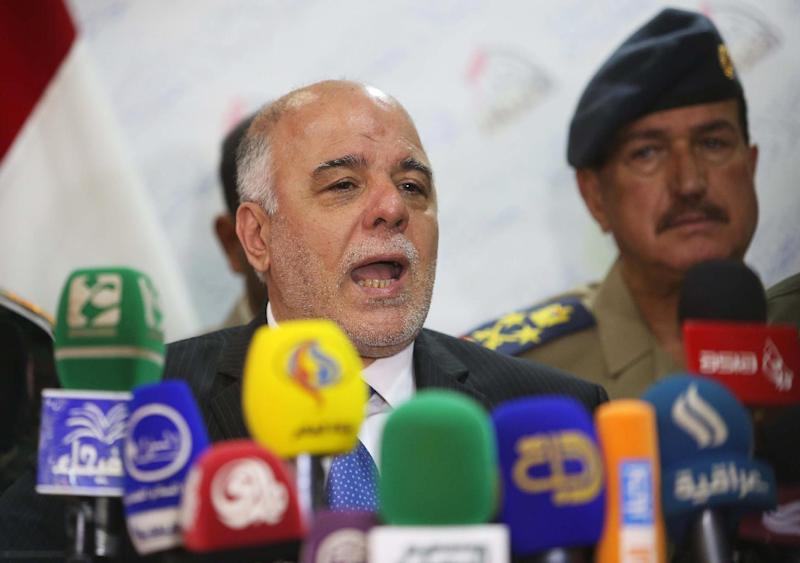 Iraqi Prime Minister Haidar al-Abadi (C) speaks during a press conference in the Shiite shrine city of Karbala in central Iraq on October 23, 2014 (AFP Photo/Mohammed Sawaf)