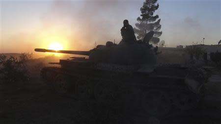 A Free Syrian Army fighter stands atop of a tank after firing towards what the FSA said were locations controlled by forces loyal to Syria's President Bashar al-Assad in the eastern Hama countryside