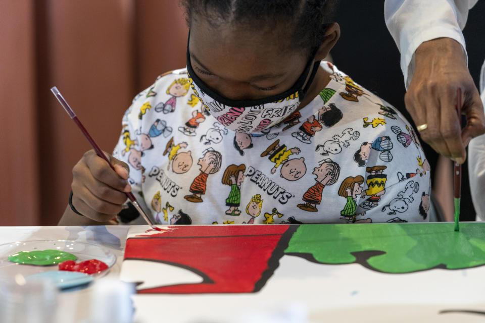 "Kerrin McCarthy, 14 , paints a panel of a ""Peanuts"" mural that will be placed in the outpatient pediatric floor of One Brooklyn Health at Brookdale Hospital, Thursday, Oct. 1, 2020, in the Brooklyn borough of New York. The beloved comic marks its 70th anniversary this week with new lesson plans, a new TV show and a philanthropic push that includes donating ""Peanuts"" murals for kids to paint in 70 children's hospitals around the globe, from Brooklyn to Brazil.(AP Photo/Mary Altaffer)"
