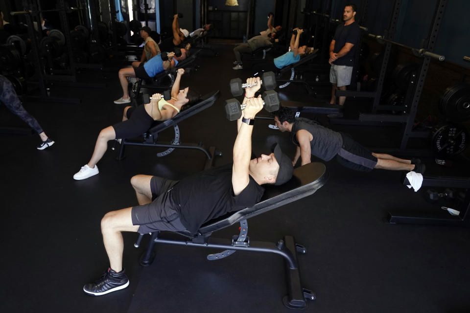 A group participates in a fitness class at Lift Society Friday, May 21, 2021, in Studio City, Calif. California's top health official says the state no longer will require social distancing and will allow full capacity for businesses when the state reopens on June 15. (AP Photo/Marcio Jose Sanchez)