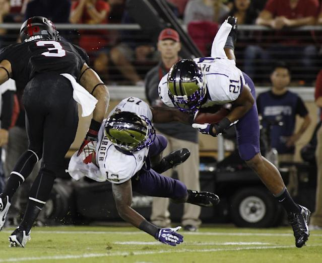 Washington's Marcus Peters, right, makes an interception against Stanford during the first half of an NCAA college football game in Stanford, Calif., Saturday, Oct. 5, 2013. At left are Stanford's Michael Rector and Washington's Will Shamburger. (AP Photo/George Nikitin)