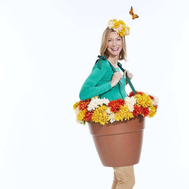 """<p>To make this out-of-the-ordinary Halloween outfit, cut bottom of plastic flowerpot with box cutter. Then, using a 1/8-inch drill bit, drill four holes for ribbon straps about three inches from center on front and back of pot. Cut four 24-inches lengths of 3/4-inch grosgrain ribbon, thread through holes, and knot them to secure. Tape fake flowers to the inside with duct tape, and top off the look with a flower crown. </p><p><a class=""""link rapid-noclick-resp"""" href=""""https://www.amazon.com/Kailin-Grosgrain-Ribbon-Multiple-Colors/dp/B07Q2MVJZR?tag=syn-yahoo-20&ascsubtag=%5Bartid%7C10070.g.490%5Bsrc%7Cyahoo-us"""" rel=""""nofollow noopener"""" target=""""_blank"""" data-ylk=""""slk:SHOP GROSGRAIN RIBBON"""">SHOP GROSGRAIN RIBBON</a></p>"""