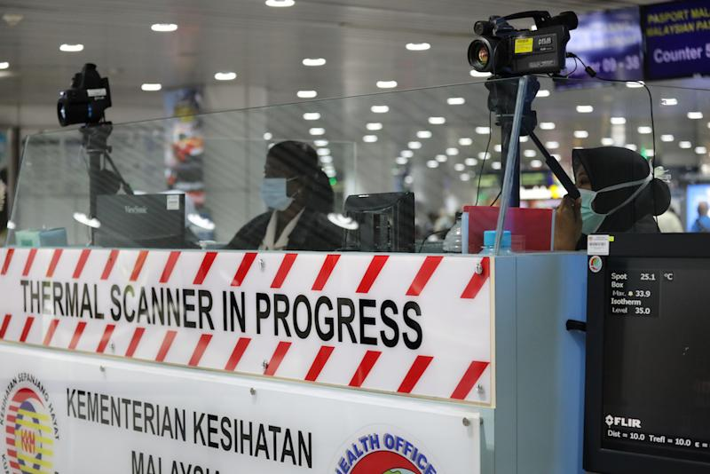 A Malaysian health quarantine officer waits for passengers at a thermal screening point at the international arrival terminal of Kuala Lumpur International Airport in Sepang January 21, 2020. — Reuters pic