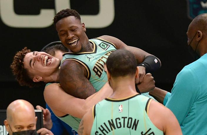 Charlotte Hornets guard Terry Rozier, center, is lifted up in the air by guard LaMelo Ball, left, as they celebrate Rozier's game-winning basket against the Golden State Warriors on Feb. 20th.