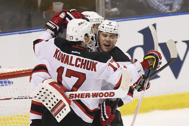 New Jersey Devils goaltender Martin Brodeur, Ilya Kovalchuk (17), Travis Zajaz (19) and Marek Zidlicky (2) celebrate their 3-2 win over the Florida Panthers in Game 1 of an NHL hockey Stanley Cup first-round playoff series in Sunrise, Fla., Friday, April 13, 2012. (AP Photo/J Pat Carter)