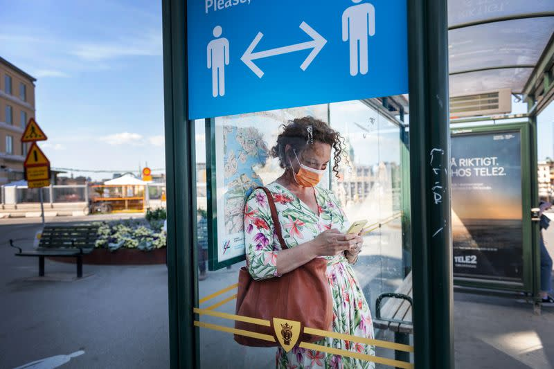 A woman wearing a face mask is seen in a bus stop next to an information sign asking people to keep social distance due to the outbreak of coronavirus disease (COVID-19), in Stockholm