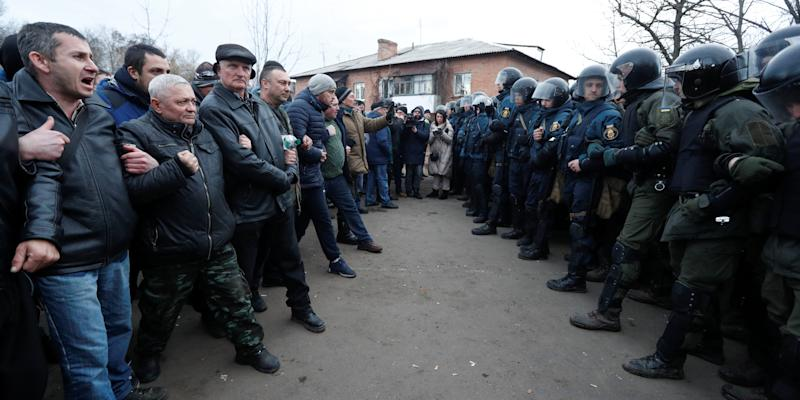 Demonstrators line up in front of Ukrainian law enforcement officers as they protest the arrival of a plane carrying evacuees from China's Hubei province hit by an outbreak of the novel coronavirus in the village of Novi Sanzhary in Poltava region, Ukraine February 20, 2020. Protesters blocked the road leading to a sanatorium where the evacuees are due to be held in quarantine for at least two weeks. REUTERS/Valentyn Ogirenko