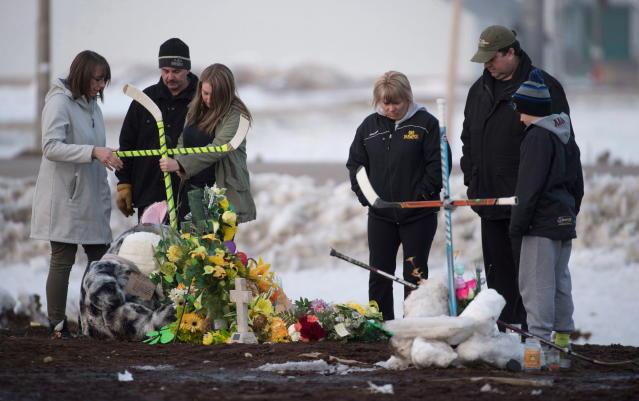 A family places a cross made from hockey sticks at a makeshift memorial at the intersection of a fatal bus crash near Tisdale, Saskatchewan, on Monday. A bus carrying the Humboldt Broncos youth hockey team crashed into a truck en route to Nipawin for a game Friday night, killing 16. (AP/Canadian Press)