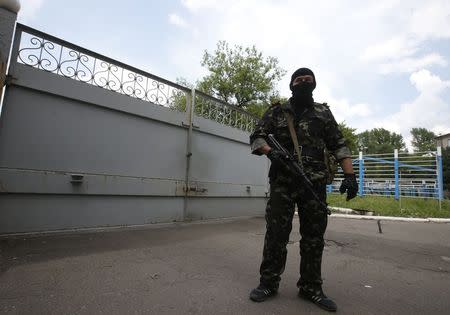 A pro-Russian separatist stands guard near the gates of a base in the east Ukrainian city of Donetsk May 30, 2014. REUTERS/Maxim Zmeyev