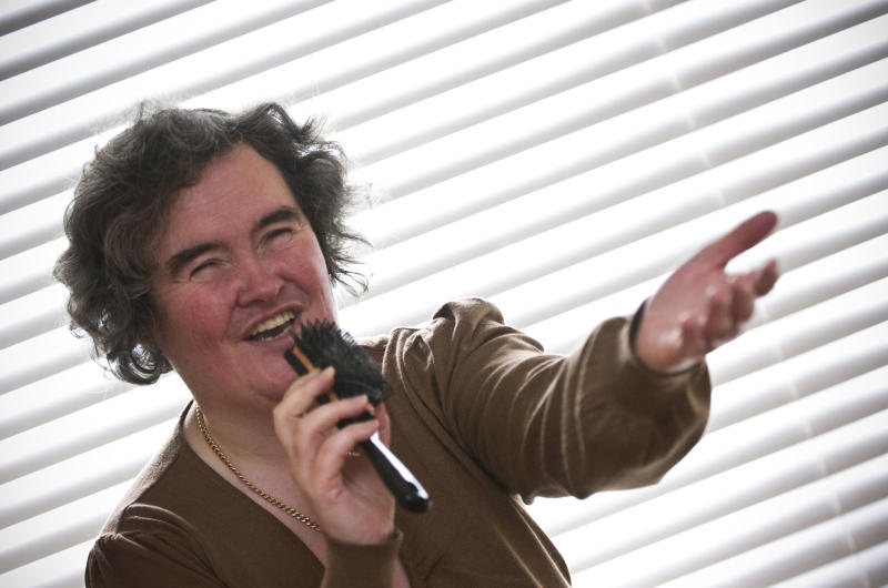 """FILE - In this April 16, 2009 file photo, Susan Boyle, whose performance on the television show """"Britain's Got Talent"""" wowed the judges, poses singing with a hairbrush at her home in Blackburn, Scotland. But what happened next for Susan Boyle? The middle-aged church volunteer from a small town in Scotland became an instant global celebrity in 2009 with her heart-stopping rendition of the """"Les Miserables"""" number """"I Dreamed a Dream"""" on a TV talent show. A week is a long time in showbiz _ and in our hyper-speed online age three and a half years is an eternity _ but Boyle is still going strong. She has sold millions of records, received an honorary doctorate, sung for Pope Benedict XVI and performed in Las Vegas. A stage musical about her life has played to enthusiastic crowds across Britain and is headed for Australia, and next month she releases her fourth album, """"Standing Ovation."""" (AP Photo, File)"""