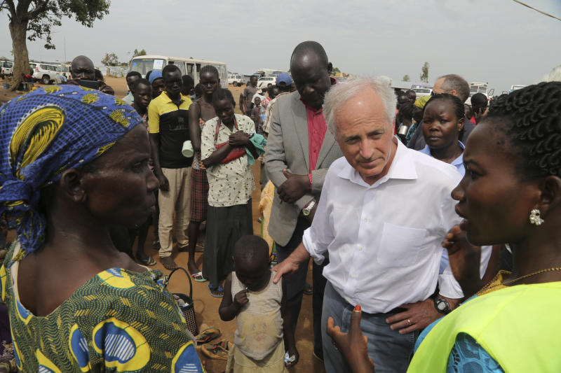 """In this photo taken on Friday April 14, 2017, U.S Senator Bob Corker, center right, speaks to recent refugees from South Sudan at a registration center in Bidi Bidi, Uganda. In a political climate dominated by President Donald Trump's slogan of """"America First,"""" two U.S. senators are proposing making American food aid more efficient after meeting with victims of South Sudan's famine and civil war. After visiting the world's largest refugee settlement in northern Uganda, Democratic Sen. Chris Coons of Delaware told The Associated Press that the U.S. """"can deliver more food aid at less cost"""" through foreign food aid reform. (AP/Photo/Justin Lynch)"""