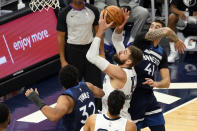 Memphis Grizzlies' Jonas Valanciunas, center, shoots past Minnesota Timberwolves' Karl-Anthony Towns (32) and Juancho Hernangomez (41) in the second half of an NBA basketball game, Wednesday, Jan. 13, 2021, in Minneapolis. The Grizzlies won 118-107. Valanciunas led the Grizzlies with 24 points. (AP Photo/Jim Mone)