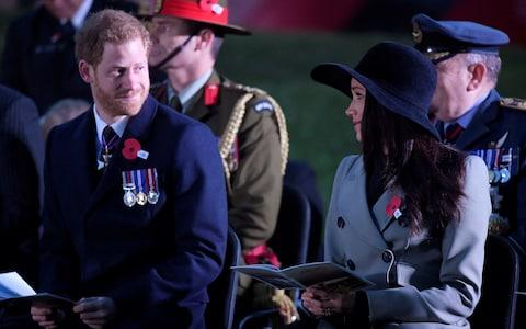 Prince Harry and Meghan Markle share a glance at the dawn service - Credit: TOBY MELVILLE /Reuters