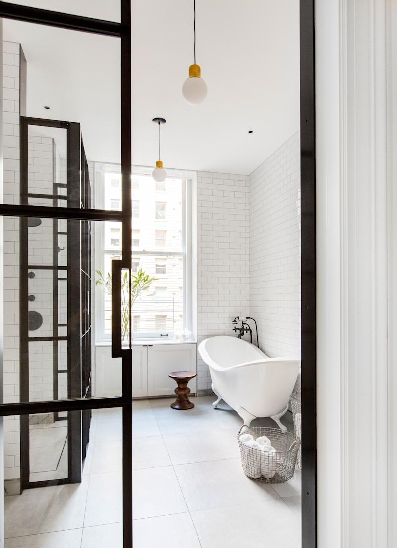 """The master bathroom—one of six bathrooms in the apartment—features iron-framed glass divisions designed by Grehl. """"We wanted very minimal, clean details that wouldn't take away from the existing architecture,"""" she says. To balance the sharp lines and masculinity of the metalwork, the designer chose a curvy claw-foot tub from Chevriot. The Eames walnut stool is from Design Within Reach."""