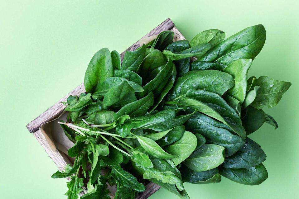 An image of spinach in a wooden crate on a green background.