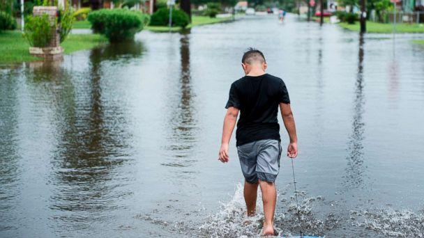 PHOTO: A boy walks with a bodyboard through a flooded street as the effects of Hurricane Harvey are seen Aug. 26, 2017 in Galveston, Texas. (Brendan Smialowski/AFP/Getty Images)