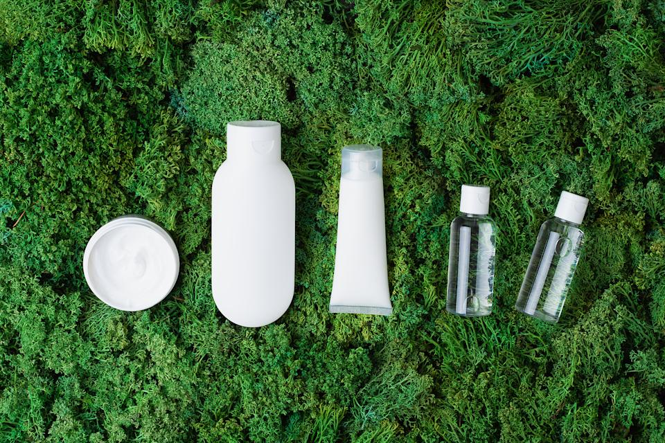 Cosmetic skin care products on green moss natural background. Flat lay, copy space