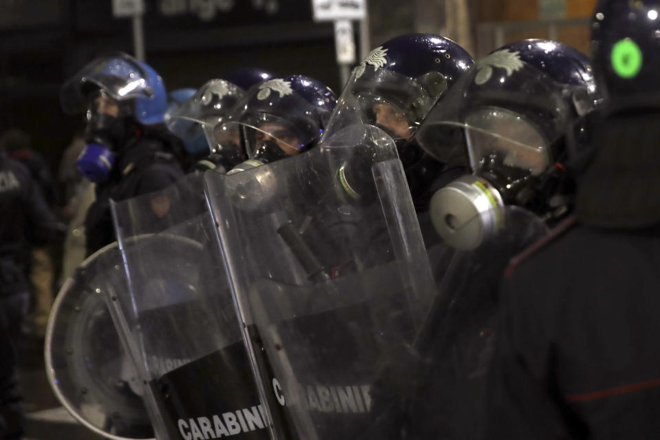 Riot police officers patrol during a protest against the government restriction measures to curb the spread of COVID-19, in Milan Italy, Monday, Oct. 26, 2020. Italy's leader has imposed at least a month of new restrictions to fight rising coronavirus infections, shutting down gyms, pools and movie theaters and putting an early curfew on cafes and restaurants. (AP Photo/Luca Bruno)