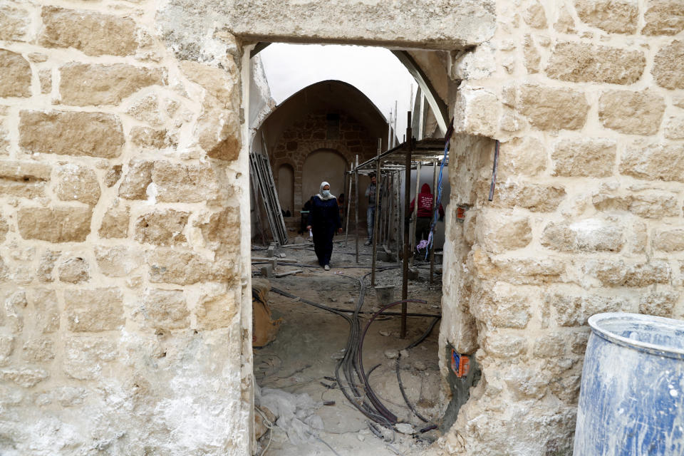An architect, center, and workers renovate the long-abandoned 200-year-old Ghussein palace, in the old quarter of Gaza City, Monday, Dec. 14, 2020. Less than 200 of these old houses are still partly or entirely standing, according to officials and they are threatened by neglect, decaying and urban sprawl. (AP Photo/Adel Hana)