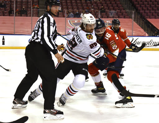Florida Panthers center Aleksander Barkov (16) battles for position with Chicago Blackhawks center Ryan Carpenter (22) after a face-off during the second period of an NHL hockey game Sunday, Jan. 17, 2021, in Sunrise, Fla. (AP Photo/Jim Rassol)