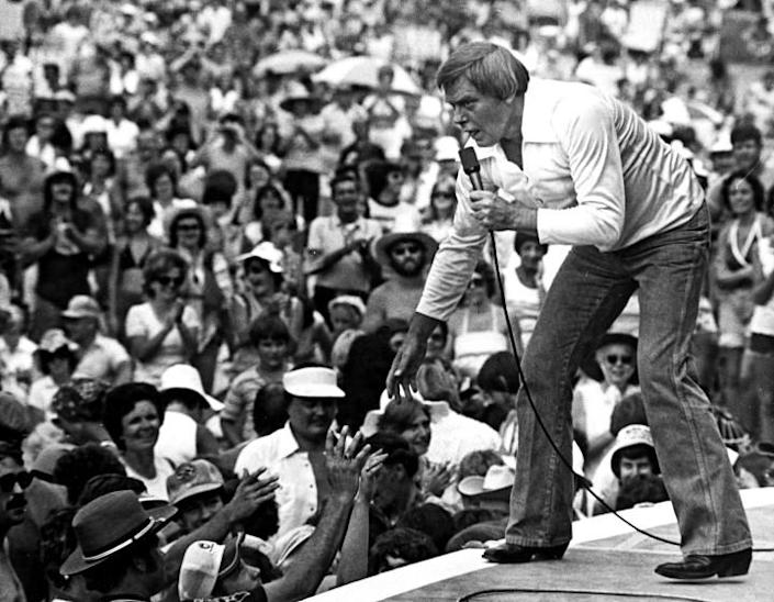 Tom T. Hall leans to the edge of the stage in 1977.