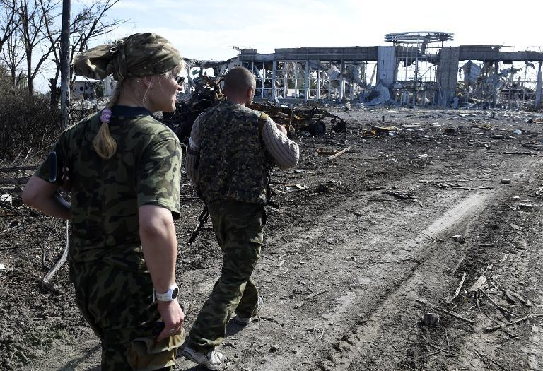 Pro-Russian militants walk in front of the remains of Lugansk International Airport, eastern Ukraine, on September 11, 2014