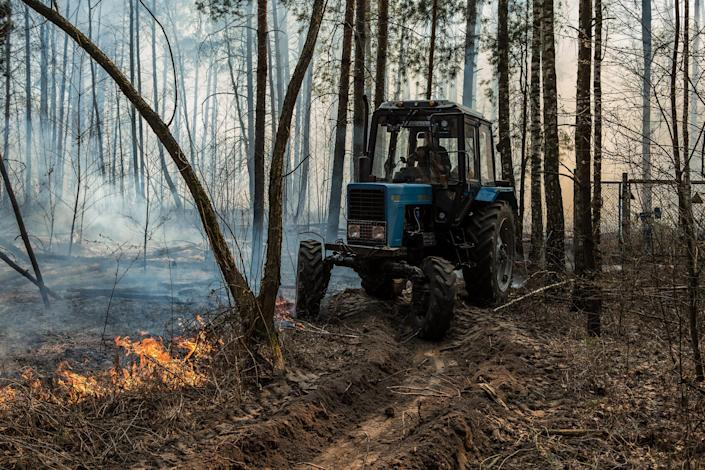 Image: A tractor operator makes a trench in the forest to prevent fire from spreading in the forest near Krasiatychi, Kyiv region, Ukraine (Oksana Parafeniuk / for NBC News)