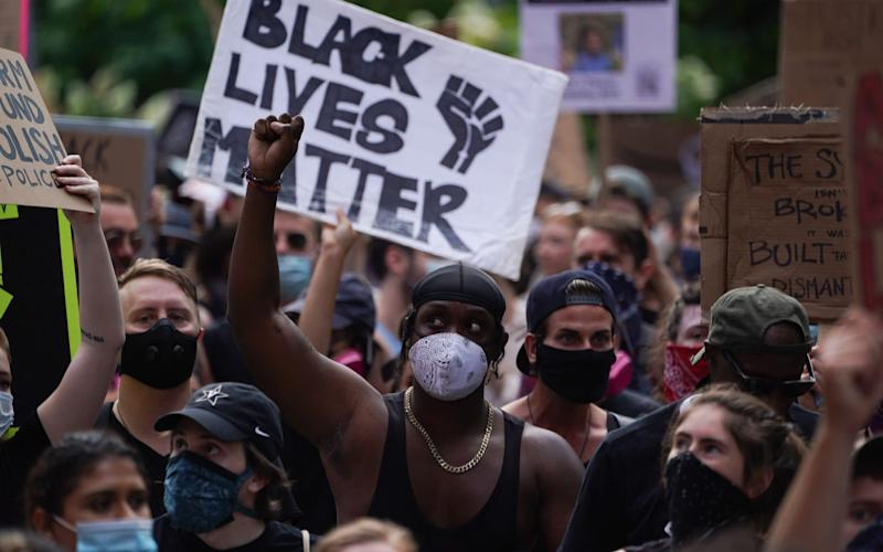 "Protesters hold a ""Black Lives Matter"" sign and raise their fists as they march through Greenwich Village in a demonstration over the death of George Floyd by Minneapolis Police on June 19, 2020 in New York. -  BRYAN R. SMITH/AFP"