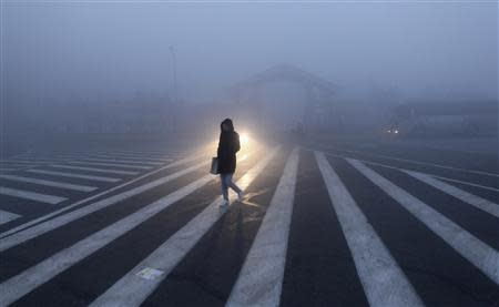 A woman walks along a street during a smoggy day in Changchun