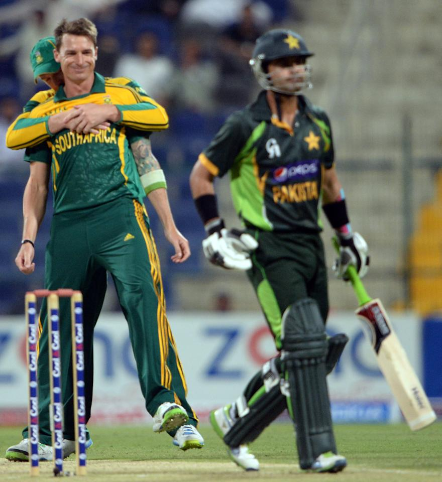 South African bowler Dale Steyn (L) celebrates with team-mate after taking a wicket of Pakistani opener Ahmad Shehzad (R) during  the third day-night international in Sheikh Zayed Cricket Stadium in Abu Dhabi on Novemver 6, 2013. Pakistan were chasing 260 runs target after South Africa made 259 runs for eight wicket in their 50 overs. The five-match series is tied at 1-1. AFP PHOTO/ Asif HASSAN        (Photo credit should read ASIF HASSAN/AFP/Getty Images)